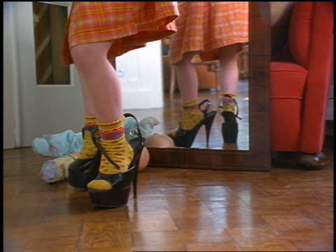 Legs of small girl putting on woman's high heel shoes + standing up + twisting feet in mirror