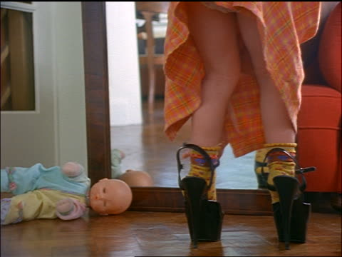 Legs of small girl strapping on woman's high heel shoes + looking in mirror