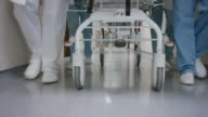 DS Legs of the medical team pushing a gurney down the hospital hallway