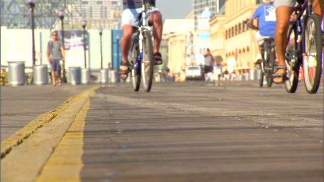Legs of two males riding bicycles through frame SOFT FOCUS female jogging up walkway w/ more people on bikes biking Healthy Lifestyle beach...