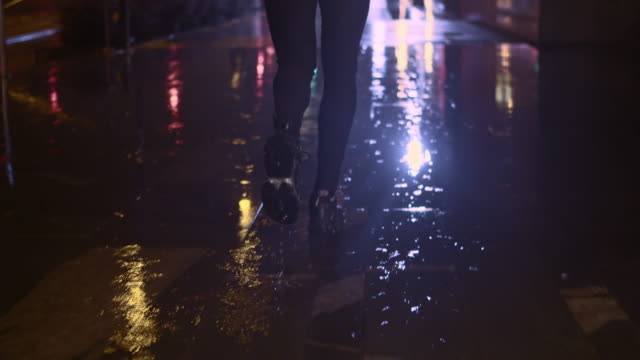 SLO MO TS Legs running in the city on rainy night