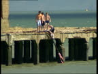 LeighonSea and SouthendonSea seaside general views Long shots of boys playing on old abandoned pier structure near sign saying 'Dangerous structure...