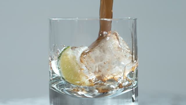 lemon falls in a glass with ice cubes together with pouring dark soda / slow motion