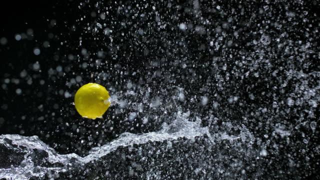 SLO MO citron flyger genom vattenstänk i luften