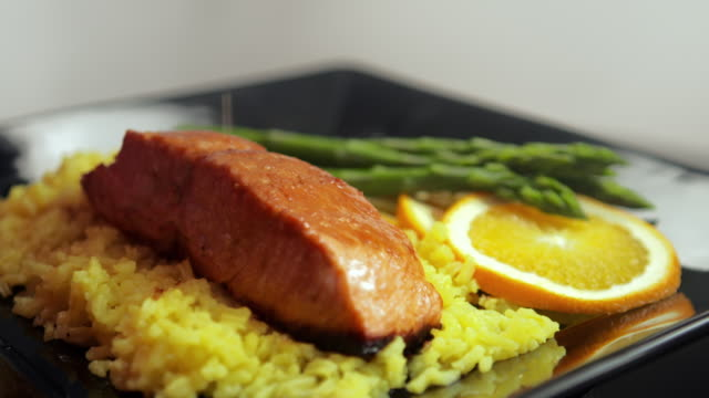 MS Lemon juice being squeezed on to cooked salmon filet / Los Angeles, California, United States