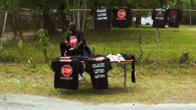 Lenny Williams and James Johnson sell teeshirts reading 'Stop Killing Us' near the spot where Walter Scott was killed on April 4th by a North...