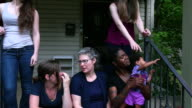 MS Lesbian couple sitting with family on front porch of home on summer evening
