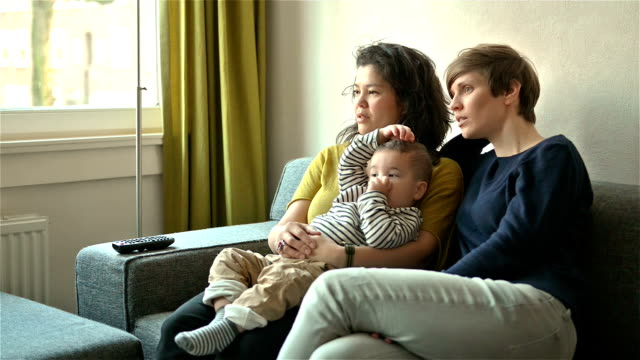 Lesbian couple watching TV with their son