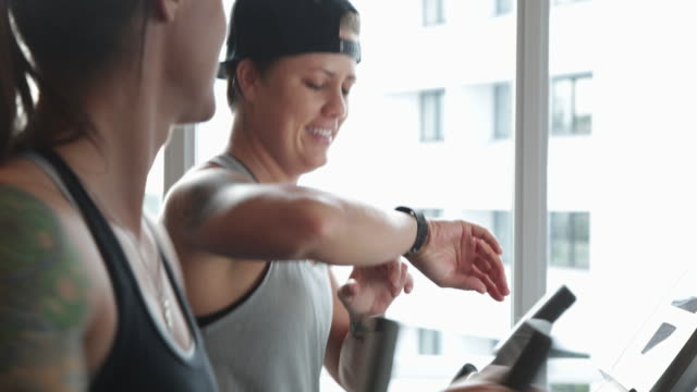 CU Lesbian couple working out in the gym, one woman checking the fitness device on her wrist.