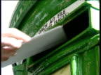 Letters being posted into green post box