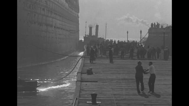 SS Leviathan slowly being pushed by several tugboats / boat at left and people on dock / title card 'A shave and a massage' / VS two groups of men on...