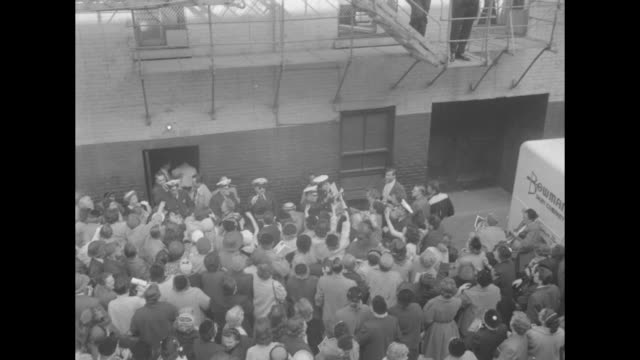 Liberace and his brother George Liberace look down from fire escape at crowd of fans below / montage police officers hand out envelopes and fans...
