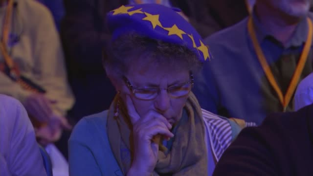 Sir Vince Cable speech Woman in the audience wearing a hat in the colours of the European Union flag Cable at podium and seen in viewfinder of...