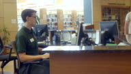 MS TS librarian working at computer terminal at help desk in public library / Rancho Mirage, California, USA