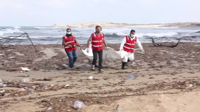 Libyan Red Crescent members remove dead bodies of refugees those washed ashore in Al Khums city of Libya on October 25 2015 A boat carrying refugees...