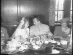 Lieutenant Tom Harmon and Elyse Knox walk out of the church handinhand towards camera / Harmon and Knox at breakfast table in wedding outfits smile...