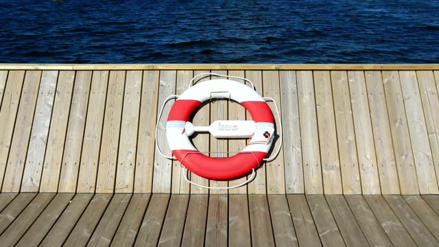 Life belt hanging on wooden pier or boat at midday