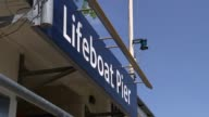 Lifeguards rescue man from Thames General view Lifeboat Pier sign Lifeboat tied to pier with City of London behind