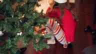 Lifestyle. Girls manipulating Christmas lights beside the Christmas tree