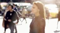 lifestyle portrait of beautiful brunette women wearing glasses. city people background