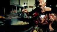 Livsstil Senior asiatisk kvinna sitter en Matlagning mat, Slow motion