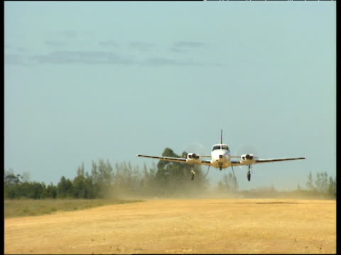 Light aircraft takes off towards camera along a dusty runway wheels fold away into undercarriage