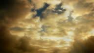 Light beams shoot through stormy clouds (Loop).