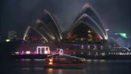 A light display flashes on a ferry in front of the Sydney Opera House on a foggy New Year's Eve.