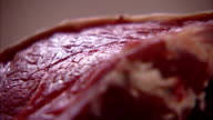 Light glistens off a cut of meat in a butcher shop in Italy. Available in HD.