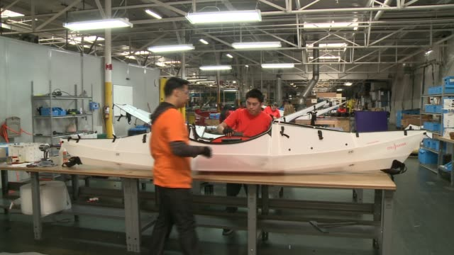 Light manufacturing plant produces hightech kayaks/ Precision machines cut parts / Workers carefully make sporting goods / Made in USA
