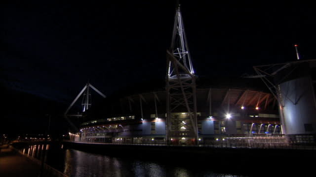 NIGHT HD VARICAM *HA TD WS Light reflecting on River Taff TU Angled WS Millennium Stadium w/ lighted modern design beam masts extending from...