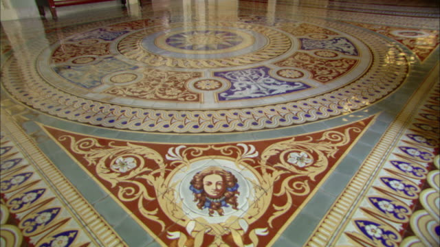 Light reflects off a shiny tiled floor near a depiction of a woman.