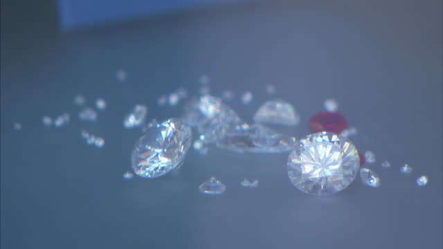 Light reflects off the facets of several diamonds.
