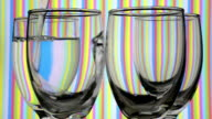 Light refraction pattern changes when filling drinking glasses with water.