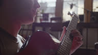 CU. Light shines off acoustic guitar as young musician picks strings and strums.