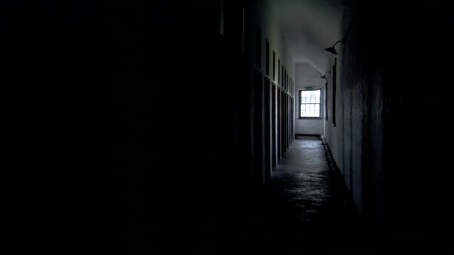 Light shines through a window at the end of a dark hallway. Available in HD.