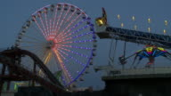 A light show on a Ferris Wheel at an Amusement Park on the Jersey Shore.  Other rides are going while  the Ferris Wheel Spins