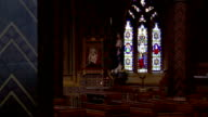 Light streams through a stained glass window at the side of an altar in St. Giles Church, Cheadle. Available in HD.