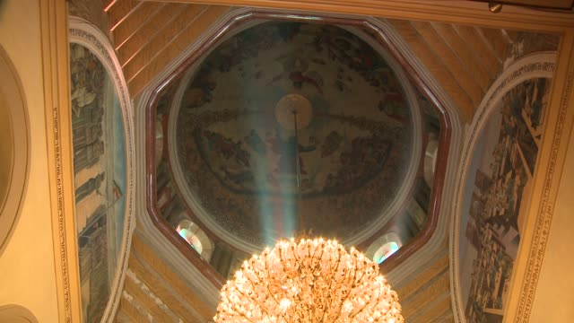 Light streams through a window above an elaborate chandelier. Available in HD.