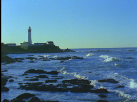 Lighthouse on rocky coastline with small waves in foreground