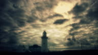 Lighthouse set against moody time lapse sky