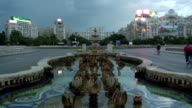 WS Lightning flashing near Unity Square Fountain in Piata Unirii and Palace of Parliament at dusk / Bucharest, Romania