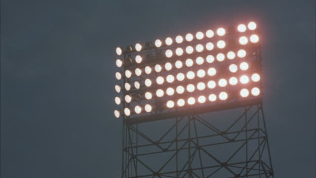 Lights flicker from the roof of a sports stadium.