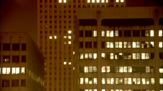 Lights illuminate the windows of office buildings. Available in HD.
