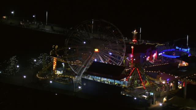 AERIAL Lights illuminating the ferris wheel and other rides at the Pacific Park Amusement Park on the Santa Monica Pier / Santa Monica, California, United States
