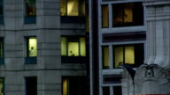 Lights shine through windows of a gray high rise building in Chicago, Illinois.