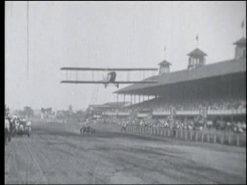 B/W PAN Lillian Boyer climbing onto ladder hanging from biplane flying past grandstand on racetrack