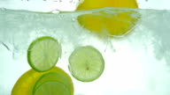 Lime, Lemon and orange slices drop in the ice water. Close up. Slow motion.