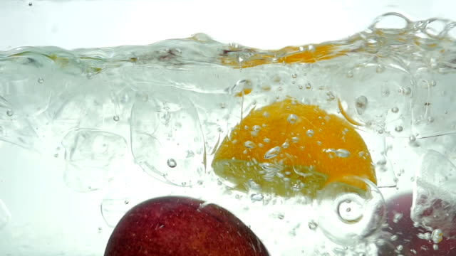 Lime orange apple and lemon drop in the ice water. Close up. Slow motion.