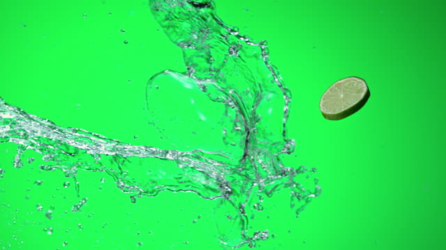 SLO MO Lime slice hitting a water splash on green background